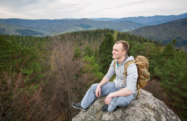 Scalatore maschio con lo zaino marrone sul picco della roccia