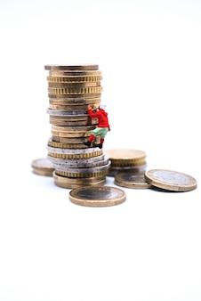 Scalatore miniatura che si arrampica sulla pila di monete