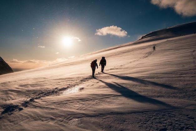 Scalatori con lo zaino che si arrampica sulla montagna nevosa