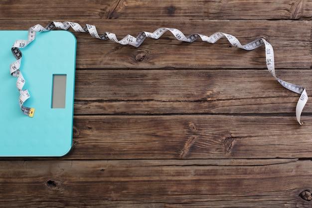Scale e nastro blu del pavimento sulla tavola di legno scura