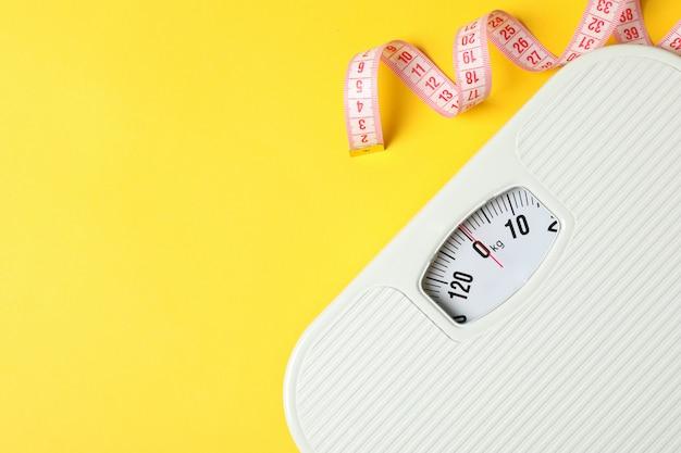 Scale e nastro di misurazione sul pavimento giallo. concetto di perdita di peso
