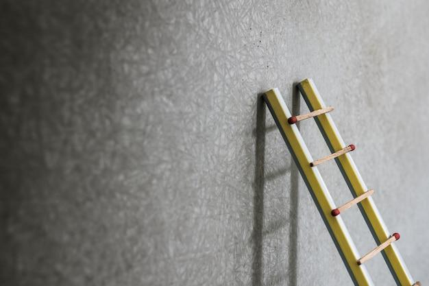 Scaletta della matita che si appoggia contro la parete del grunge con lo spazio della copia. successo o concetto di educazione.