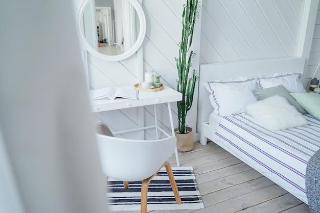 Scandinavo moderno accogliente eco interni, tavolo bianco e specchio nella camera da letto