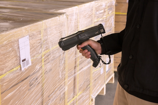 Scanner del codice a barre della tenuta del lavoratore del magazzino con la scansione su una spedizione del pallet.