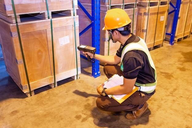 Scanner del codice a barre di scansione del lavoratore del magazzino sul pallet pesante della cassa nel magazzino di stoccaggio