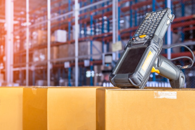 Scanner di codici a barre con scatole di cartone nel magazzino.