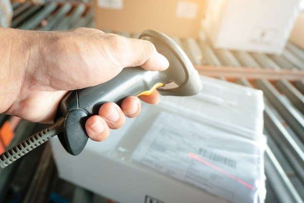 Scanner di codici a barre della tenuta della mano dell'operaio con la scansione alle scatole di un pacchetto