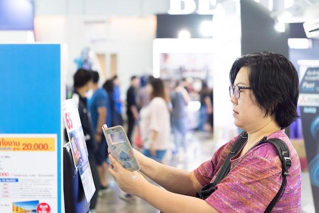Scansione qr della donna asiatica dal cellulare nel grande magazzino