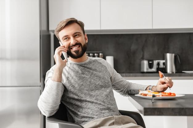 Scapolo bello 30s con la barba che ha conversazione mobile, mentre mangiando cibo sano a cena in appartamento