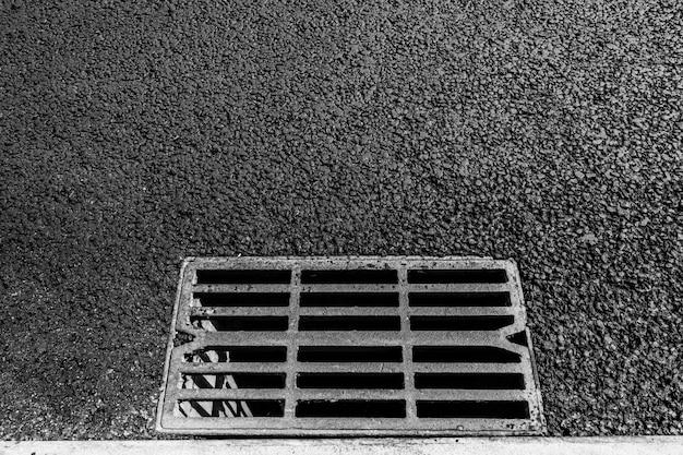 Scarico in metallo su strada asfaltata.