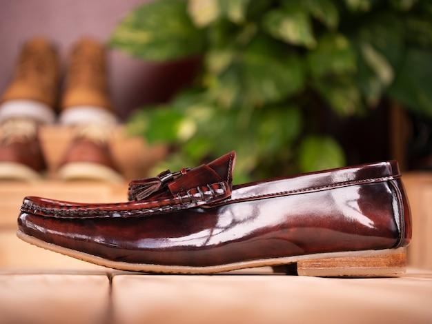 Scarpa mocassino con nappina moda uomo su legno nel negozio.