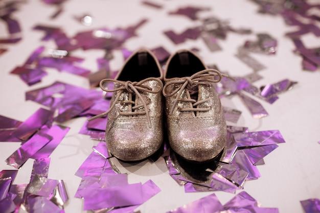 Scarpe alla moda del bambino su bianco con coriandoli colorati