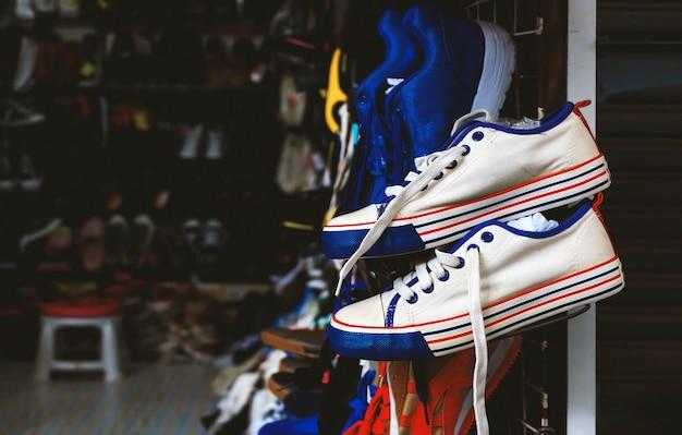 Scarpe bianche del primo piano che appendono nel negozio con il tono di colore del film soft-focus e vecchio