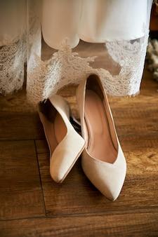Scarpe bianche della sposa di nozze del progettista nelle strisce di luce solare.