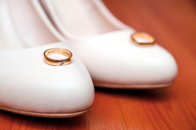 Scarpe bianche tradizionali di nozze con gli anelli su di legno.