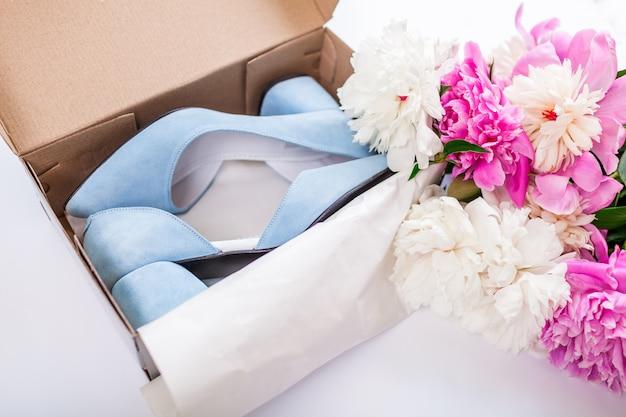 Scarpe blu femminili di nozze in scatola con i fiori su bianco