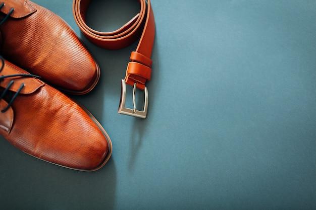 Scarpe, cintura, profumo e anelli d'oro in pelle marrone.