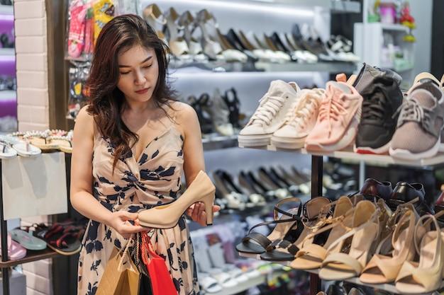 Scarpe d'acquisto del tacco alto della giovane donna in negozio