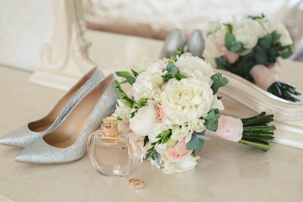 Scarpe d'argento della sposa, profumo, bouquet e fedi nuziali