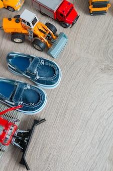 Scarpe da barca blu per ragazzo vicino set di giocattolo auto. vista dall'alto. cornice di sfondo