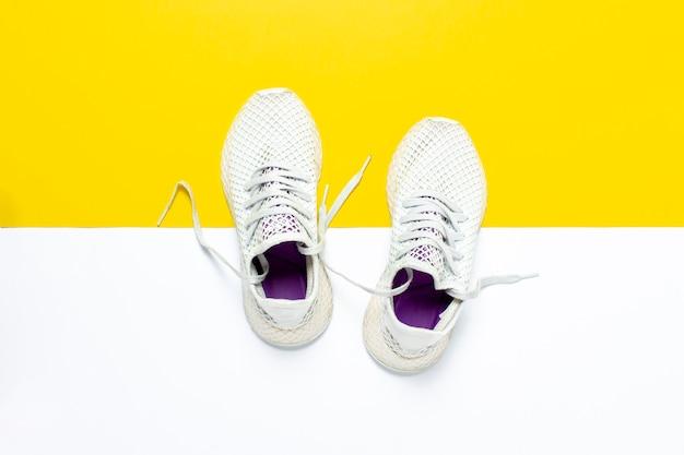Scarpe da corsa bianche su una superficie giallo-bianca astratta. concetto di corsa, allenamento, sport. . vista piana, vista dall'alto