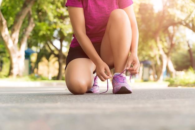Scarpe da corsa - corridore di fitness sport femminile sta preparando per fare jogging in giardino