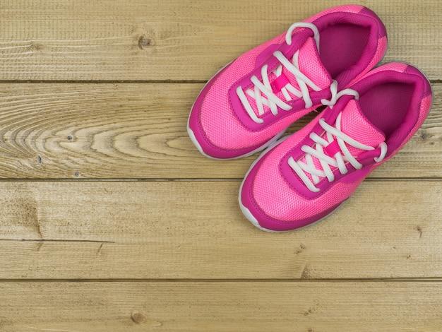 Scarpe da corsa delle belle donne rosa d'annata sul pavimento. la vista dall'alto.