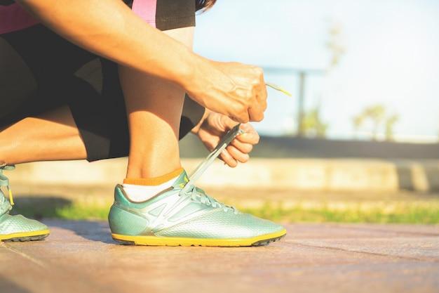 Scarpe da corsa - donna che lega i lacci delle scarpe. primo piano del corridore femminile di forma fisica di sport che si prepara per pareggiare all'aperto.
