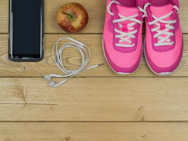 Scarpe da corsa rosa per lezioni di fitness in palestra e una mela sul pavimento di legno. vista dall'alto