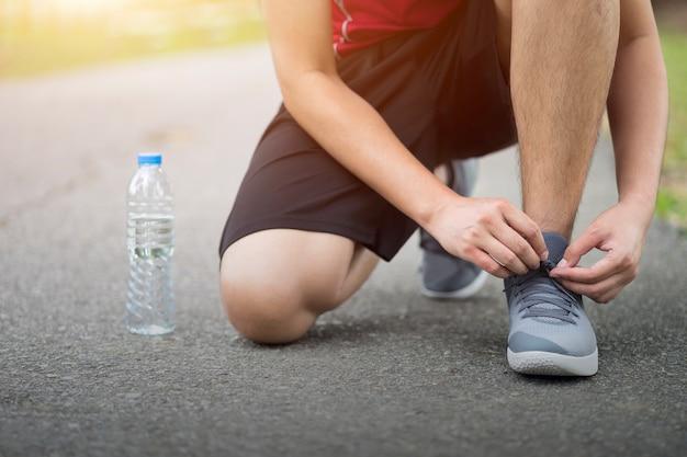 Scarpe da corsa - uomo ginocchio con sneakers cravatta shoestring, runner man si prepara per fare jogging in giardino.