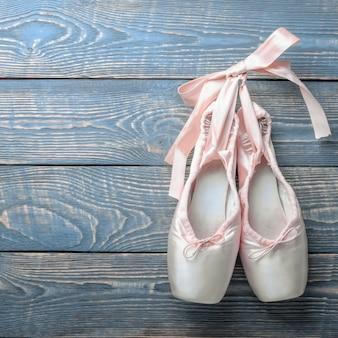 Scarpe da danza classica con un fiocco di nastri appesi a un chiodo su legno