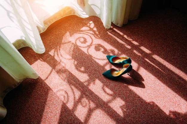 Scarpe da donna con tacco alto in pelle scamosciata si trovano sul pavimento in una stanza d'albergo. la luce del sole cade dalla finestra, la mattina prima del matrimonio.