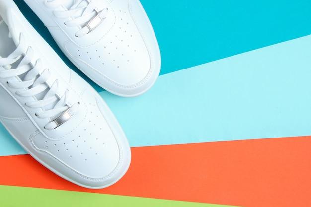 Scarpe da ginnastica bianche su un tavolo di carta colorata.