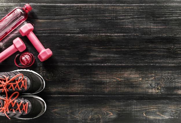 Scarpe da ginnastica con manubri e una bottiglia d'acqua. vista piatta. tutto in un unico colore.