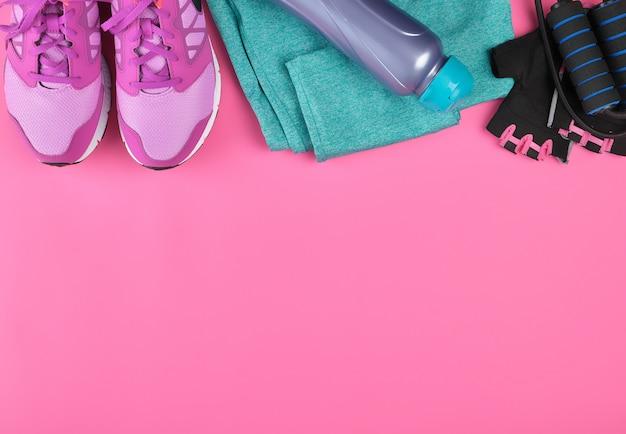 Scarpe da ginnastica da donna rosa, una bottiglia d'acqua, guanti e una corda per saltare per lo sport