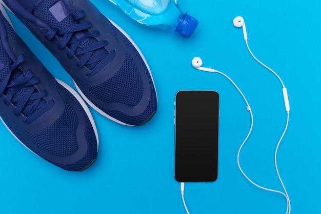 Scarpe da ginnastica e cellulare con le cuffie