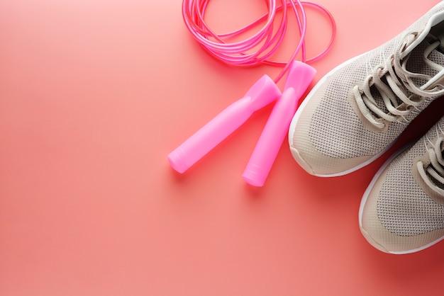 Scarpe da ginnastica e corda per saltare su sfondo rosa