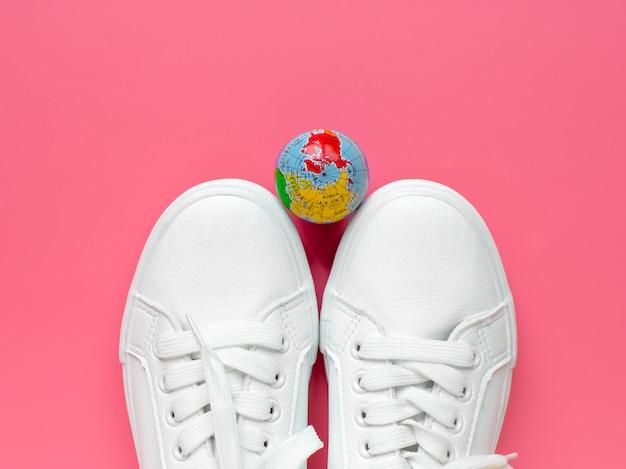 Scarpe da ginnastica e il globo su uno sfondo rosa. stile di vita. concetto di viaggio vista dall'alto. distesi.