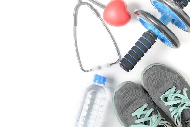Scarpe da ginnastica e ruota di fitness con stetoscopio isolato