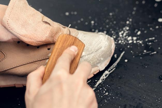 Scarpe da ginnastica in un lavandino con acqua insaponata. lavare le scarpe da ginnastica sporche, pulire le scarpe in officina