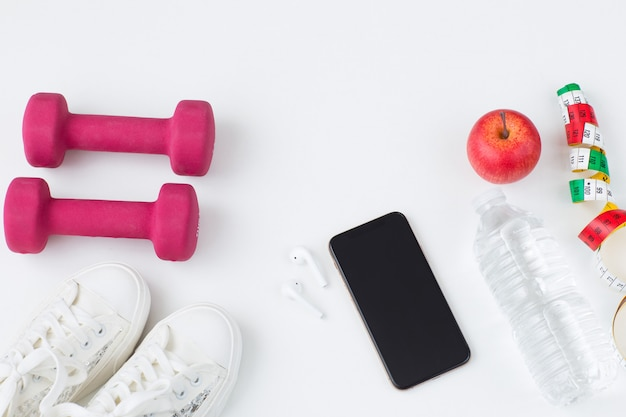 Scarpe da ginnastica, manubri, telefono, cuffie wireless, acqua in bottiglia, mela e metro