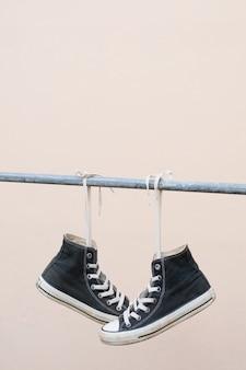 Scarpe da ginnastica nere appese alla barra di metallo
