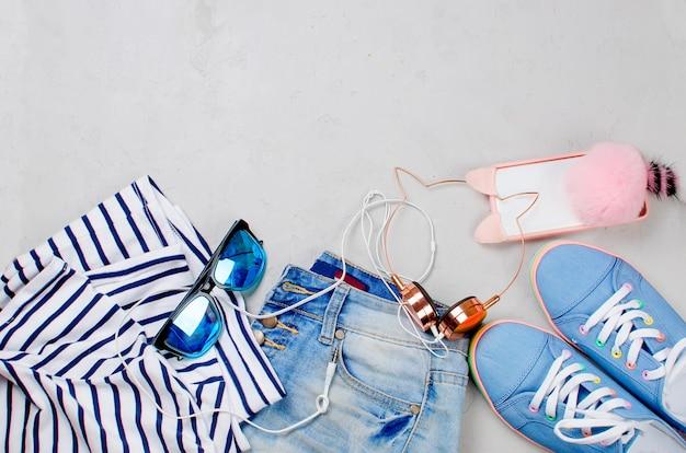 Scarpe da ginnastica, pantaloncini, occhiali da sole, telefono e auricolari