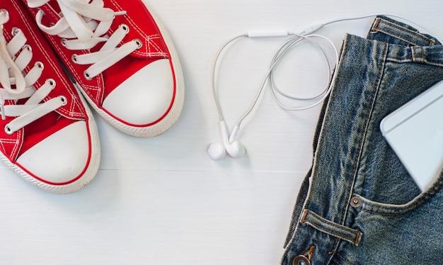 Scarpe da ginnastica rosse con blue jeans, uno smartphone in tasca, una vista dall'alto
