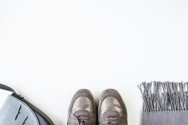 Scarpe da ginnastica, sciarpa e borsa femminili grige su un fondo bianco