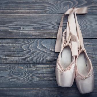 Scarpe da punta scarpe da ballo con un fiocco di nastri appesi a un chiodo su un legno.