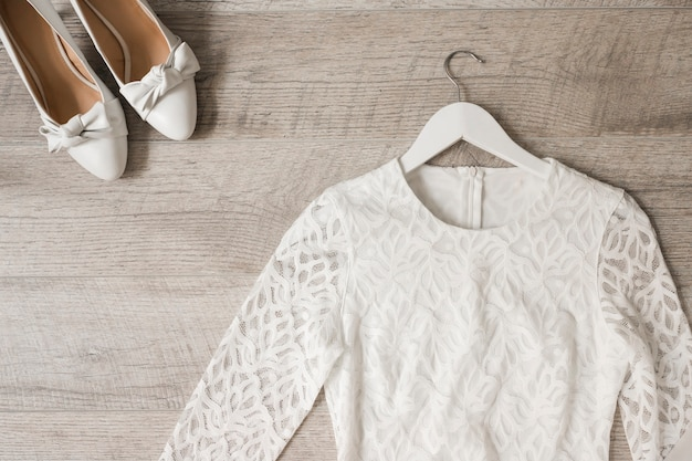 Scarpe da sposa bianche vestito da sposa e vestito su fondo di legno