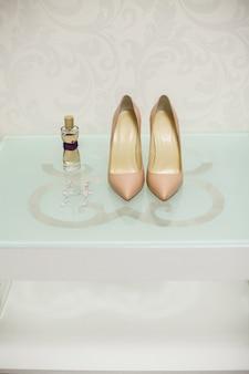 Scarpe da sposa bianco crema su un tavolo di vetro. spirits. orecchini.
