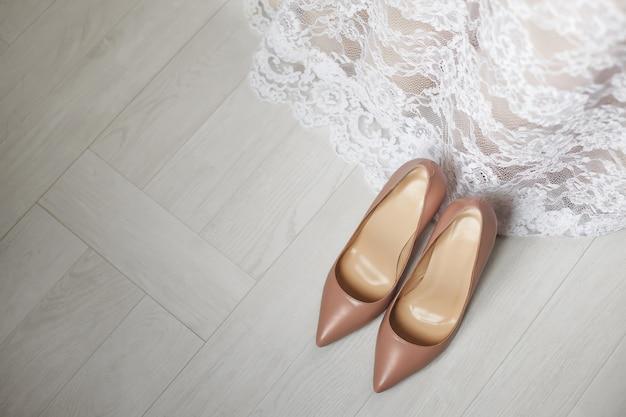 Scarpe da sposa color crema sul pavimento. vestito da sposa.