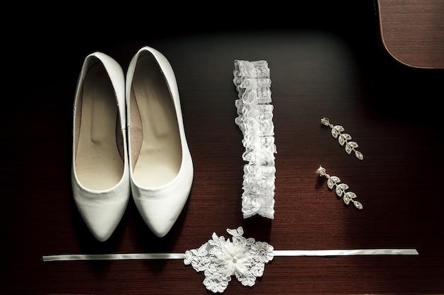 Scarpe da sposa da donna bianche, giarrettiera, orecchini su fondo in legno scuro.